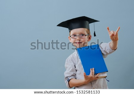 Cute smiling little ginger boy in glasses, wearing student hat holds stack of books in hands over blue background. Half length. He's making rock-n-roll gesture, to show he's cool. Foto stock ©