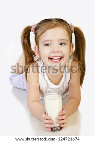 Cute smiling little girl is drinking milk isolated over white