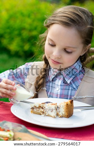 cute smiling little girl sitting by dinner table and eating cake. Kid eats healthy food. Fine dinning.