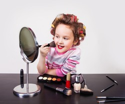 cute smiling little girl with makeup brush