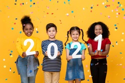 Cute smiling mixed race kids showing numbers 2021 celebrating new year isolated on yellow background