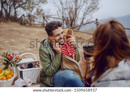 Cute smiling overjoyed mixed race man sitting on blanket and posing with dog while his girlfriend taking picture of them. Picnic at autumn concept.