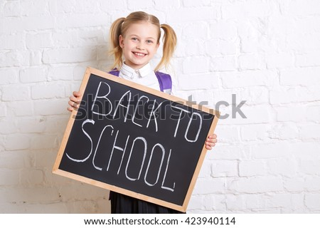 Cute smiling schoolgirl in uniform standing with blackboard and smiling on light  background. Back to school.