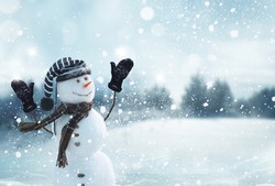 Cute smiling snowman with striped hat and scarf. Winter fairytale.Snowfall in the magic forest.Merry christmas and happy new year greeting card with copy-space