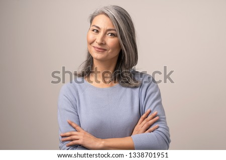 Cute Smiling Woman With Grey Hair Bends Her Head, Looks At Camera While Having Her Arms Crossed. Beautiful Middle-Aged Asian Woman With Crossed Arms. Portrait. Studio Photoshoot
