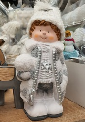 Cute snowflake girl in white wool cap, silver-white coat, white boots holding snowball. Selected focus.