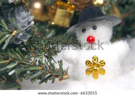 cute snowman to a dark hat in an environment of snowdrifts and christmas evergreen trees