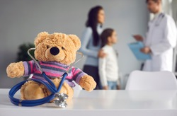 Cute soft teddy bear doctor with stethoscope sitting on table at pediatric clinic or children's medical center. Kids checkup visit to hospital, health maintenance concept. Blurred empty space for text