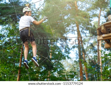 cute, sporty boy in white t shirt in the adventure rope activity park with helmet and safety equipment. Young boy playing and having fun doing activities outdoors. Hobby, active lifestyle concept #1153779124