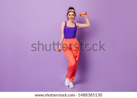 Cute sporty girl in bright fitness outfit in style of 80s with smile demonstrates exercises with dumbbells