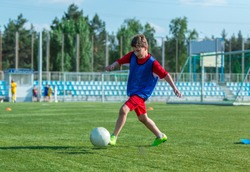 cute, sporty kid in red uniform trains dribbling  on the summer football stadium. sport, active lifestyle concept