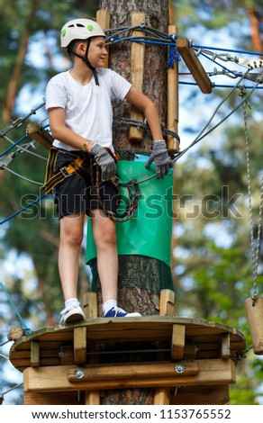 cute, sporty, young boy  in white t shirt in the adventure activity park with helmet and safety equipment. Young boy playing and having fun doing activities outdoors. Hobby, active lifestyle concept #1153765552