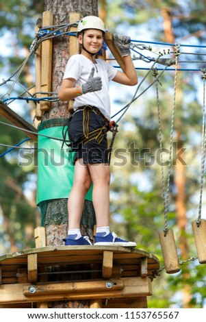 cute, sporty, young boy  in white t shirt in the adventure activity park with helmet and safety equipment. Young boy playing and having fun doing activities outdoors. Hobby, active lifestyle concept #1153765567