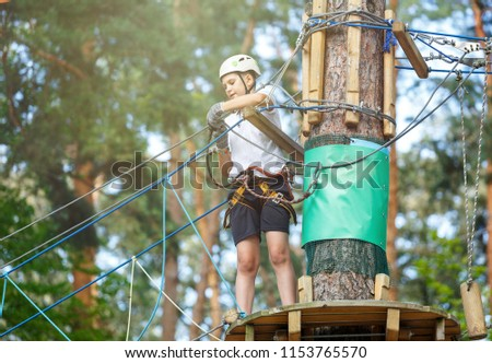 cute, sporty, young boy  in white t shirt in the adventure activity park with helmet and safety equipment. Young boy playing and having fun doing activities outdoors. Hobby, active lifestyle concept #1153765570