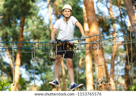 cute, sporty, young boy  in white t shirt in the adventure activity park with helmet and safety equipment. Young boy playing and having fun doing activities outdoors. Hobby, active lifestyle concept #1153765576