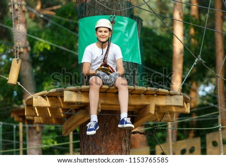 cute, sporty, young boy  in white t shirt in the adventure activity park with helmet and safety equipment. Young boy playing and having fun doing activities outdoors. Hobby, active lifestyle concept #1153765585