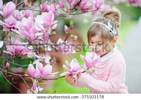 Stock Photo Cute spring  fashion girl under blossom magnolia tree