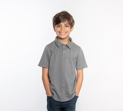 Cute standing young boy in gray polo shirt hands in pockets