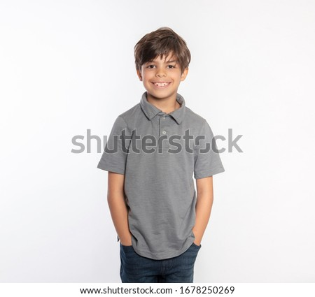 Cute standing young boy in gray polo shirt hands in pockets Stock photo ©