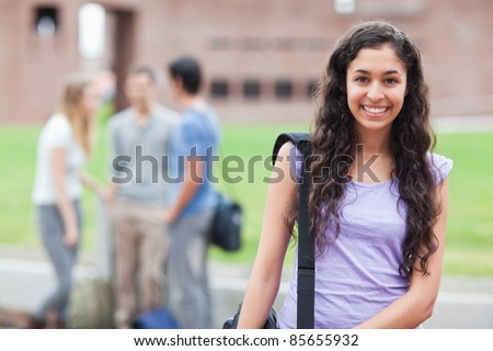 Cute student posing while his classmates are talking in a yard