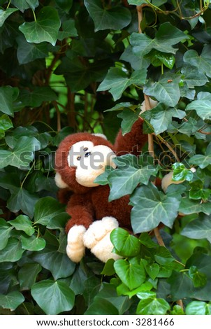cute stuffed animal monkey swinging in tree with ivy