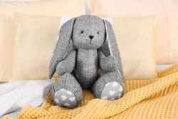 Cute stuffed toy rabbit on comfortable bed in child's room interior