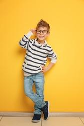 Cute stylish boy near color wall