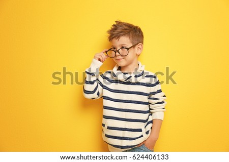 Cute stylish boy on color background