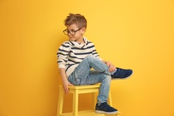 Cute stylish boy sitting on chair near color wall