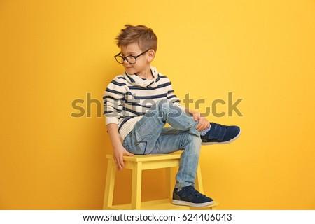 Cute stylish boy sitting on chair near color wall #624406043