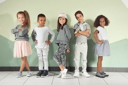 Cute stylish children near color wall