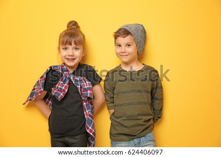Cute stylish children on color background
