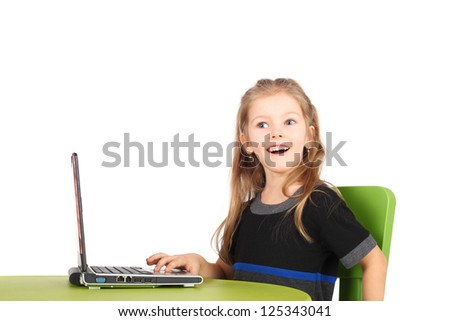 cute surprised little girl playing with the computer