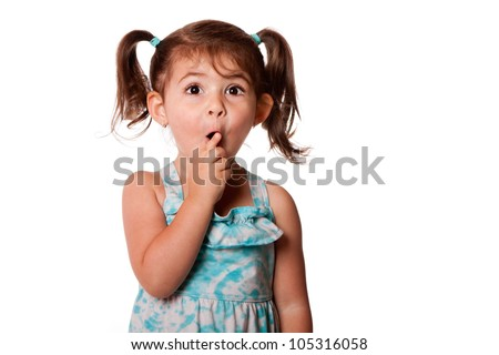 Cute surprised little toddler girl with finger in front of mouth making silence shhh gesture, isolated.