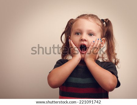 Cute surprising child girl with opened mouth and hand near the face looking on empty copy space. Vintage portrait