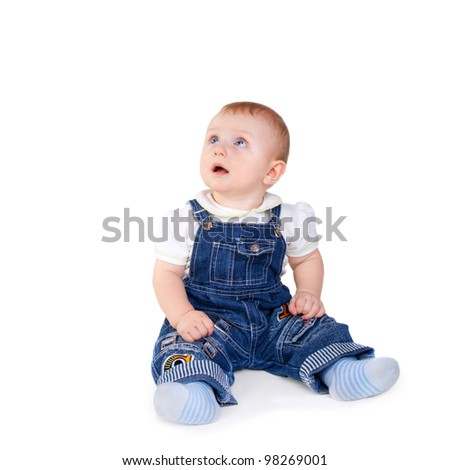 cute sweet little baby in jeans overalls sitting on the floor