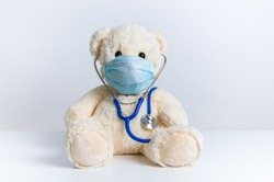 Cute teddy bear doctor with protective medical mask and stethoscope. Concept of pediatric treatment of illness, hygiene, epidemic and virus protection for child patient. Fluffy toy on white background
