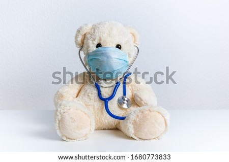 Cute teddy bear doctor with protective medical mask and stethoscope. Concept of pediatric treatment of illness, hygiene, epidemic and virus protection for child patient. Fluffy toy on white background Zdjęcia stock ©