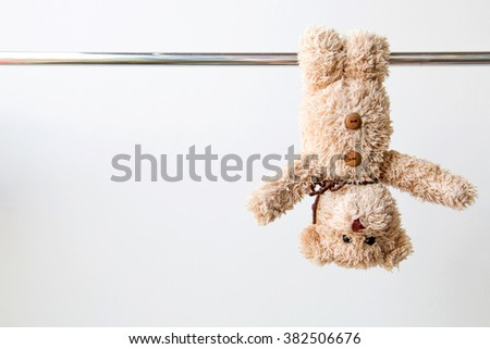 Cute teddy bear is hanging on steel rail ,He exercise for fit and firm. #382506676