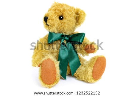 Cute teddy bear is sitting and looking to left, toy is made from golden mohair complemented with pure wool