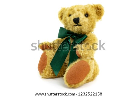Cute teddy bear is sitting, toy is made from golden mohair complemented with pure wool