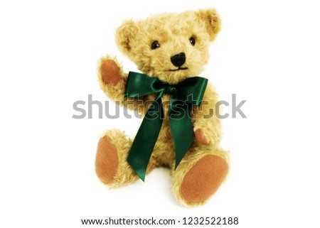 Cute teddy bear is sitting with raise paw, toy is made from golden mohair complemented with pure wool