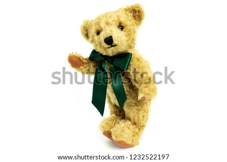 Cute teddy bear is standing with raised paw, toy is made from golden mohair complemented with pure wool