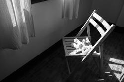 Cute teddy bear lying alone on chair near window,black and white tone