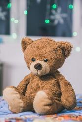 Cute teddy bear sitting on the bed