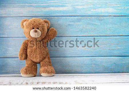 Cute teddy bear with copy space on blue color wood background. #1463582240