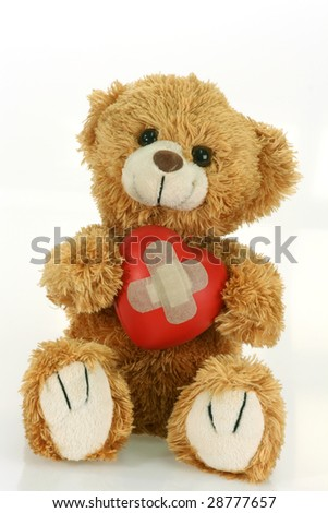 Cute teddy bear with decorative heart on bright background - stock photo