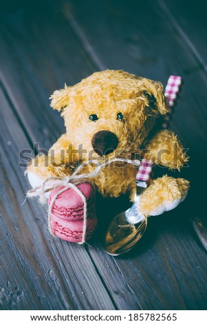 Cute teddy bear with lovely macaroon sweet little biscuit for romantic present.