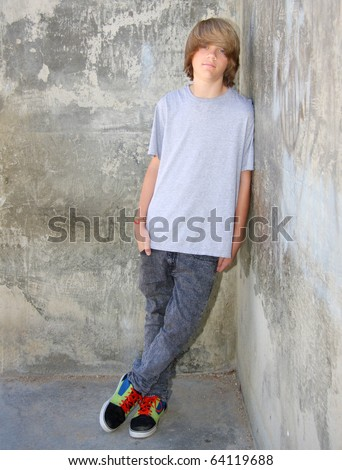 Cute teen boy leaning against a cement wall.
