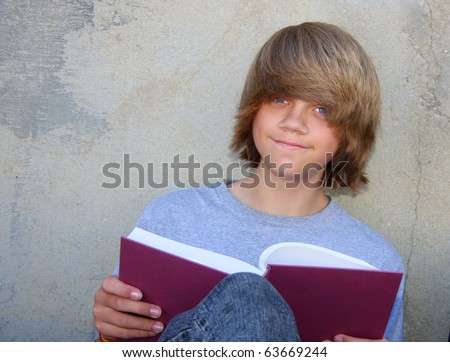 Cute teen boy sitting against a cement wall reading a book. - stock